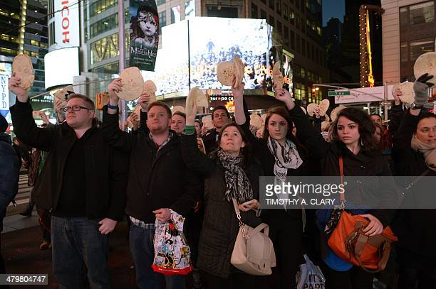 Supporters hold Pita bread during a flash mob in Times Square March 20 2014 as a image of crowds of Palestinians lining up for UN Relief and Works...