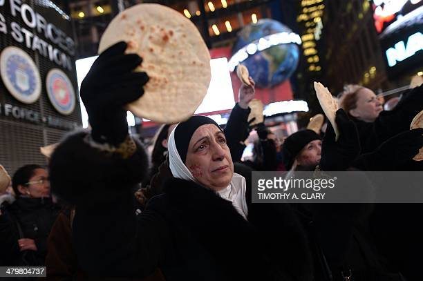 Supporters hold Pita bread during a flash mob on Times Square March 20 2014 as an image of crowds of Palestinians lining up for UN Relief and Works...