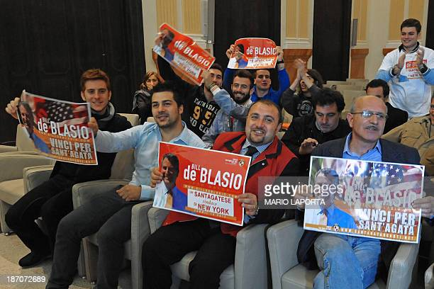 Supporters hold posters of Bill de Blasio candidate for New York's mayor at his electoral support committee office as they look at the results on a...