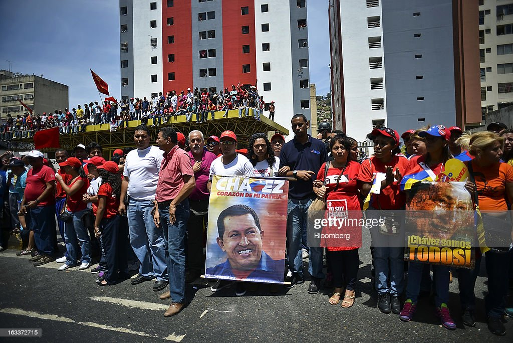 Supporters hold posters while gathering to pay their respects during the funeral for Venezuelan President Hugo Chavez in Caracas, Venezuela, on Friday, March 8, 2013. Allies of Venezuela's Hugo Chavez paid their final respects to the firebrand socialist leader at a state funeral that marked the emotional high point of a week of tributes preceding a snap election to choose his successor. Photographer: Meridith Kohut/Bloomberg via Getty Images