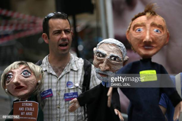 Supporters hold puppets of Britain's Prime Minister Theresa May Labour leader Jeremy Corbyn and Liberal Democrat leader Tim Farron during a protest...