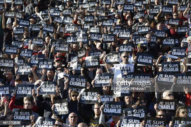 Supporters hold signs reading 'Je suis Charlie' to pay tribute to the people killed on January 7 in the attack by two armed gunmen of the offices of...