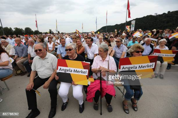 Supporters hold signs while waiting for the start of an election campaign rally with Angela Merkel Germany's chancellor and Christian Democratic...