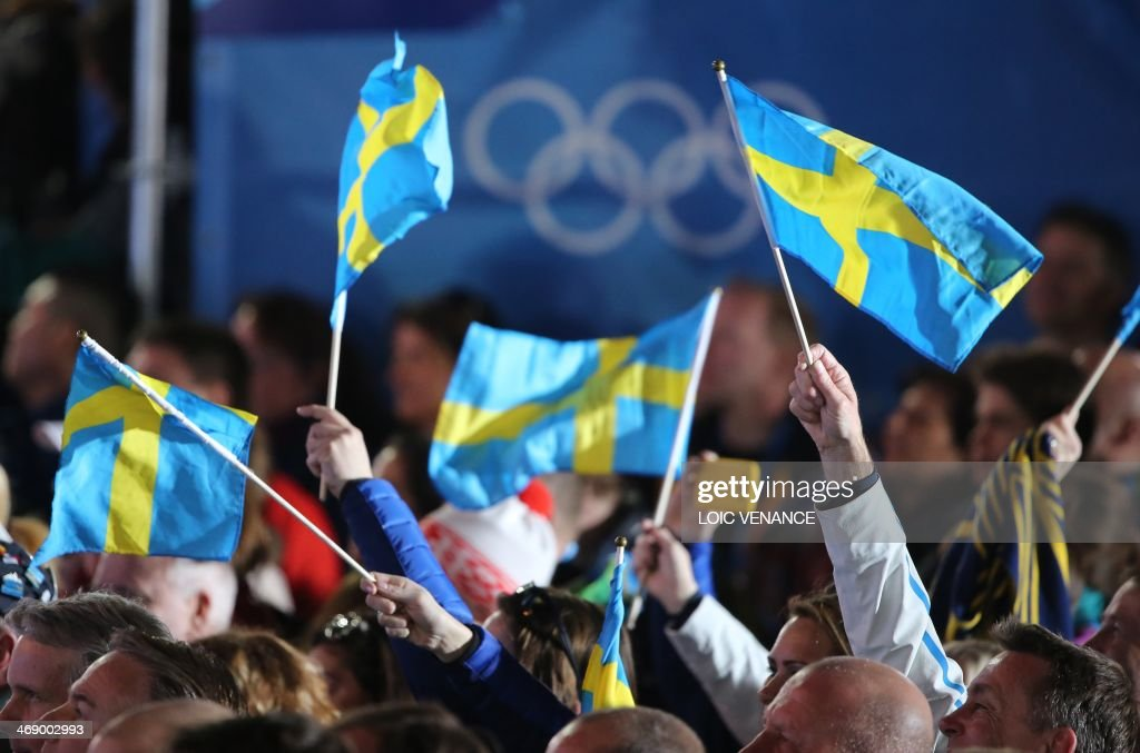 Supporters hold Swedish flags during a Medal Ceremony at the Sochi medals plaza during the Sochi Winter Olympics on February 12, 2014. AFP PHOTO / LOIC VENANCE