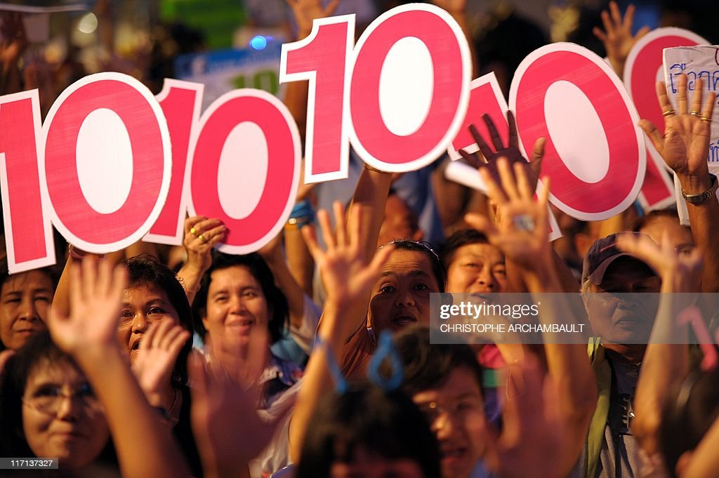 Supporters hold up '10' signs during a rally by Thailand's ruling party held at the site of a deadly military crackdown on opposition 'Red Shirt'...