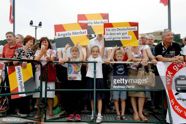 Supporters hold up a signs saying 'Angela Merkel' during an election rally at the headland known as the 'Deutsches Eck' where the Mosel and Rhine...