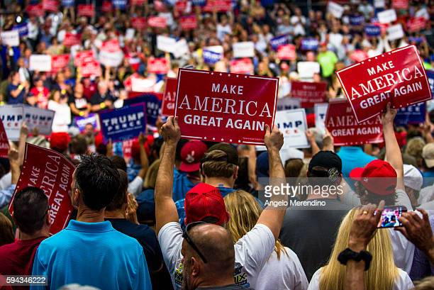 Supporters hold up signs during a campaign rally of Republican presidential nominee Donald Trump at the James A Rhodes Arena on August 22 2016 in...
