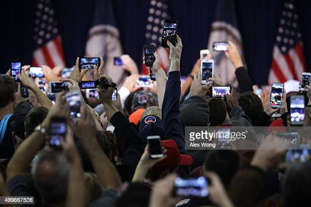 Supporters hold up their phone cameras as they wait for the arrival of Republican presidential candidate Donald Trump at a campaign rally December 2...