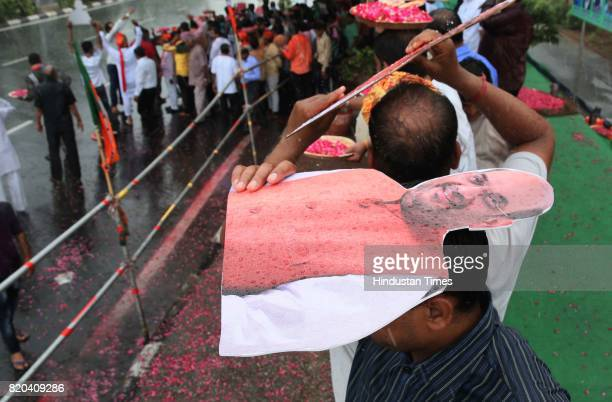 Supporters huddle under cutout of BJP National President Amit Shah during sudden showers while waiting to welcome him on his way in a procession from...