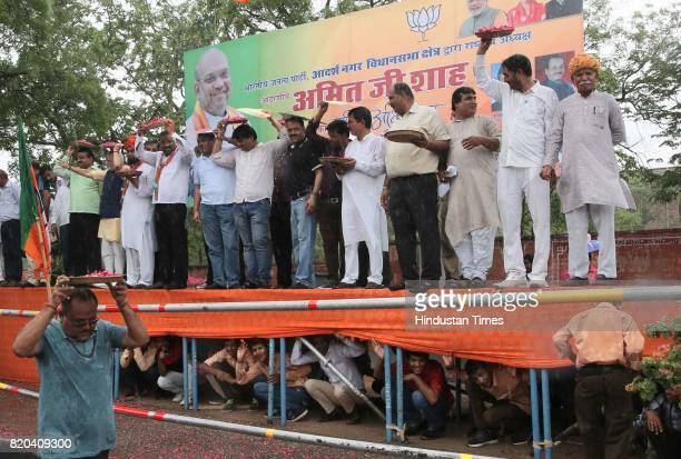 Supporters huddle under stage during sudden shower while waiting to welcome BJP National President Amit Shah on his way in a procession from Sanganer...