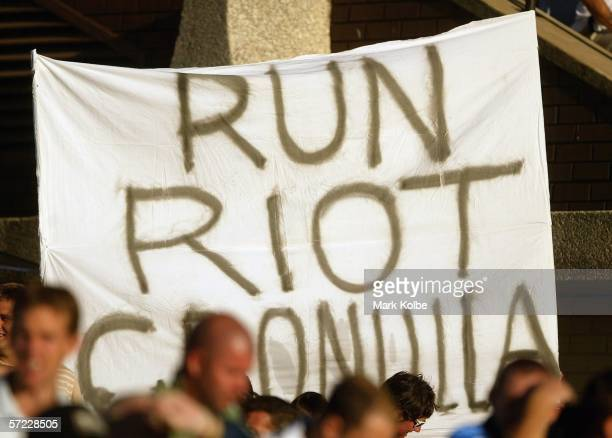 Supporters in the crowd hold up a banner in reference to the riots on Crunulla Beach during the round four NRL match between the CronullaSutherland...