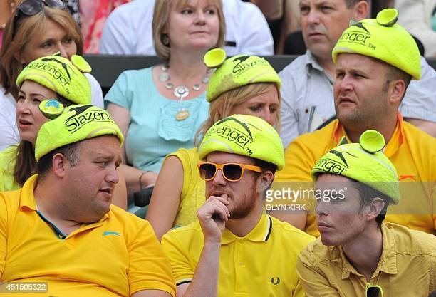 Supporters in yellow tennis ball costumes sit in the crowd on centre court on day seven of the 2014 Wimbledon Championships at The All England Tennis...