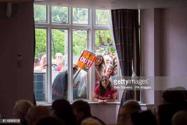 Supporters lean through an open window to get a glimpse of Labour leader Jeremy Corbyn speaking at the Bournemouth West Cliff Hotel during a visit to...