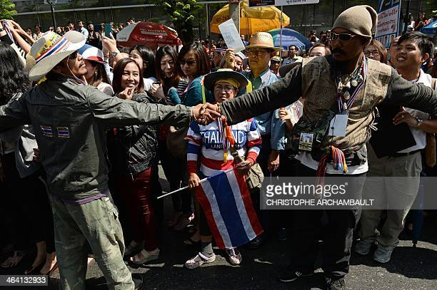 Supporters line the streets as security guards hold hands and form a chain around Thai protest leader Suthep Thaugsuban as antigovernment protesters...