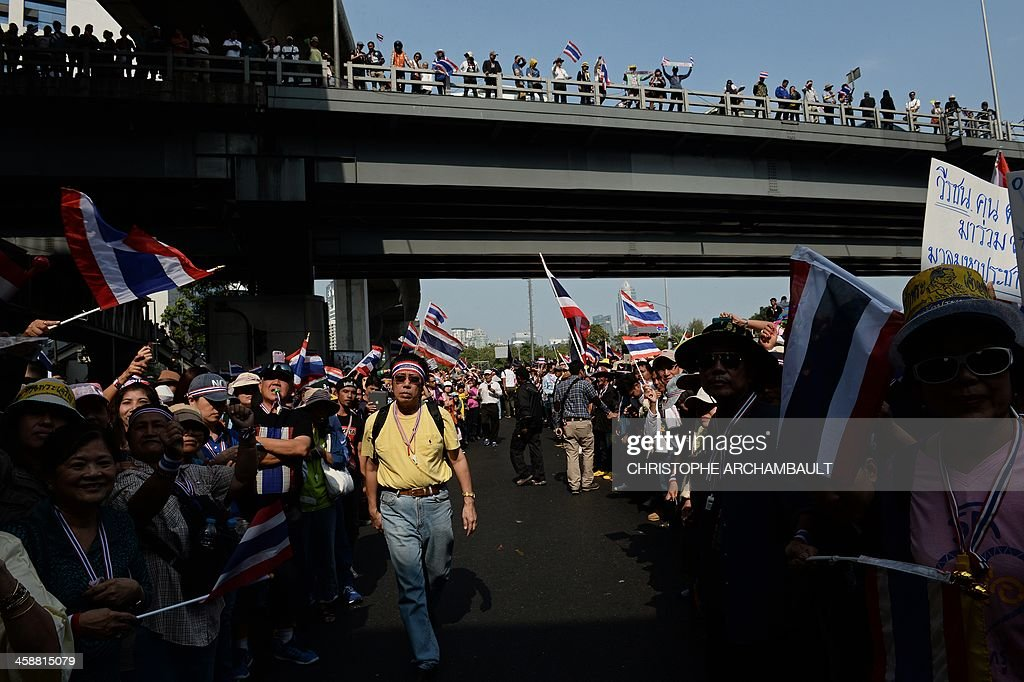 Supporters line up the streets during a march by Thai anti-government protesters through Bangkok as part of their ongoing rally on December 22, 2013. Tens of thousands of Thai anti-government protesters massed ahead of a major rally on December 22 aimed at toppling the premier, paralysing parts of central Bangkok a day after the main opposition party declared a boycott of snap polls. AFP PHOTO/Christophe ARCHAMBAULT