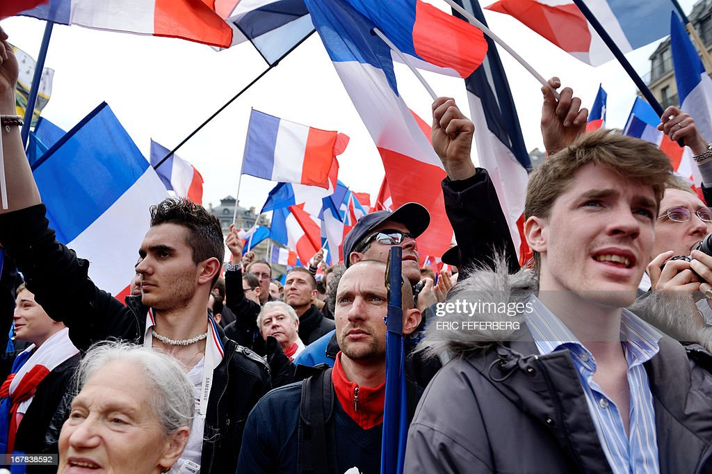 Supporters listen to French far right Front National (FN) party president Marine Le Pen as she speaks as part of the party's annual celebrations of Joan of Arc on May 1, 2013 on Paris' Opera square.