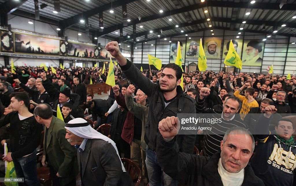 Supporters listen to the speech of Hezbollah leader Hassan Nasrallah during a memorial service for the senior Hezbollah commander Hassan Lakkis on December 20, 2013 in Beirut, Lebanon. Lakkis was killed outside his home in Beirut's Saint Therese district as he returned from work on December 4. Hezbollah has accused Israel of standing behind the killing, noting that the self-proclaimed Jewish state had made several previous unsuccessful attempts on Lakkis' life.