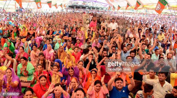BJP supporters listening to Uttar Pradesh Chief Minister Yogi Adityanath during the closing ceremony of BJP's Parivartan Rath Yatra on July 10 2017...