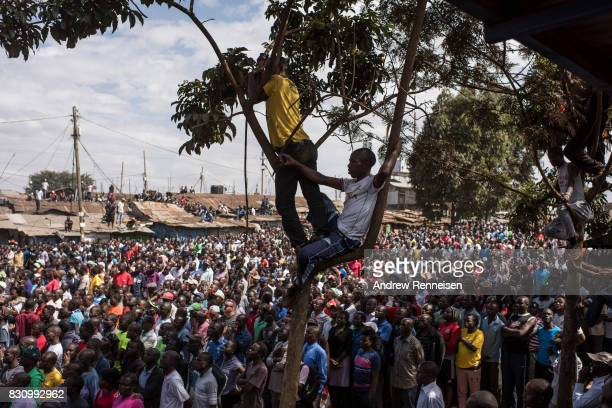 Supporters look on as opposition candidate Raila Odinga addresses a crowd in the Kibera slum on August 13 2017 in Nairobi Kenya A day prior...