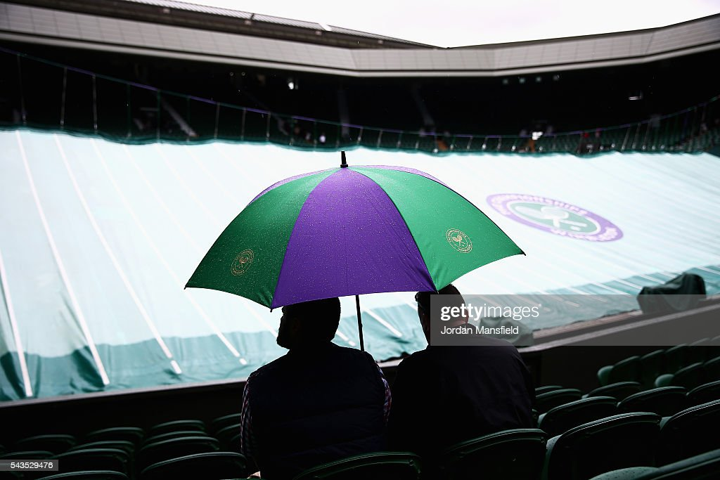supporters look on from under their umbrellas as court one is covered due to rain on day three of the Wimbledon Lawn Tennis Championships at the All England Lawn Tennis and Croquet Club on June 29, 2016 in London, England.