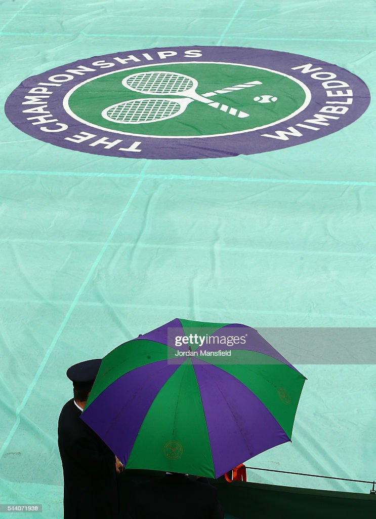 Supporters look on from under their umbrellas as the courts are covered on day five of the Wimbledon Lawn Tennis Championships at the All England Lawn Tennis and Croquet Club on July 1, 2016 in London, England.