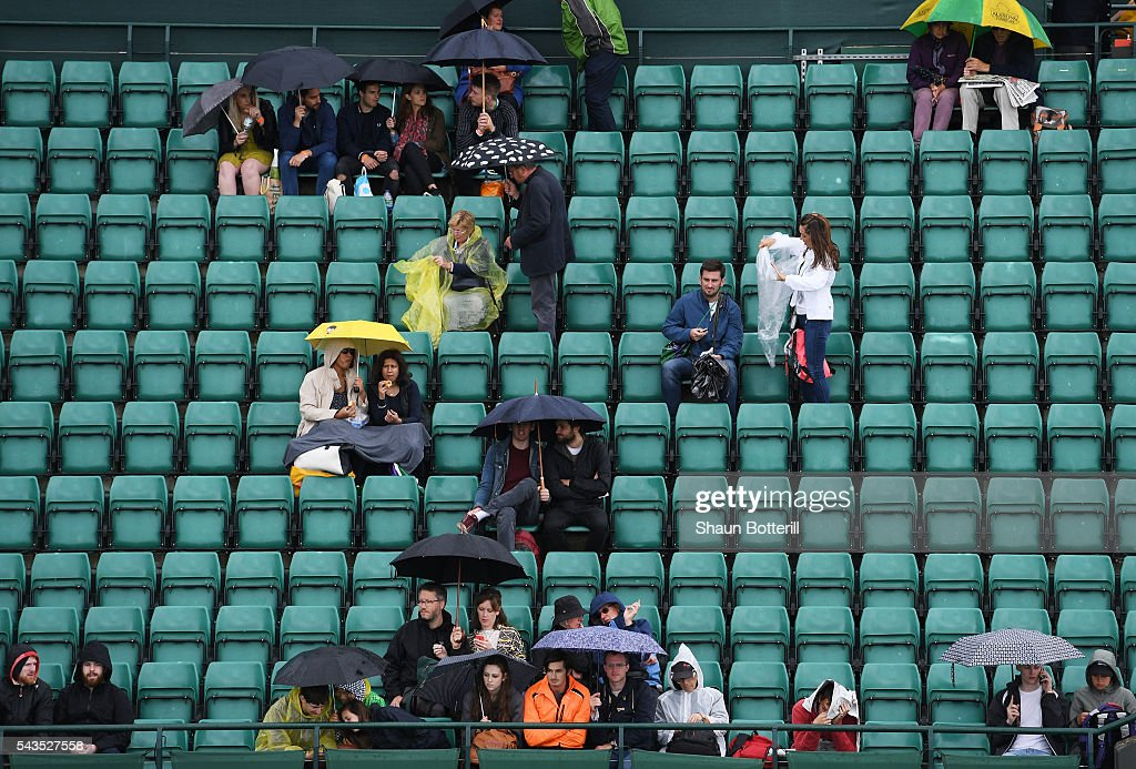 supporters look on from under their umbrellas as the outdoor courts are covered due to rain on day three of the Wimbledon Lawn Tennis Championships at the All England Lawn Tennis and Croquet Club on June 29, 2016 in London, England.