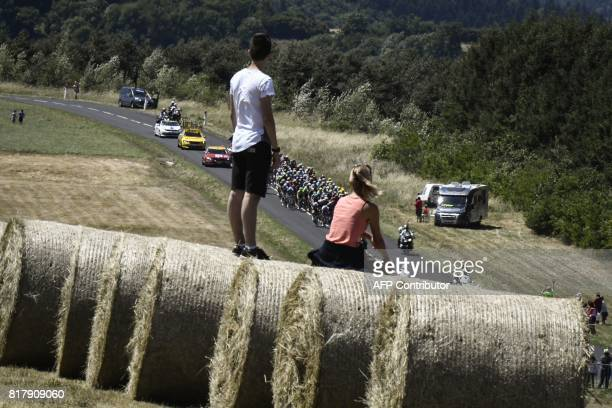 Supporters looks at the pack riding during the 165 km sixteenth stage of the 104th edition of the Tour de France cycling race on July 18 2017 between...
