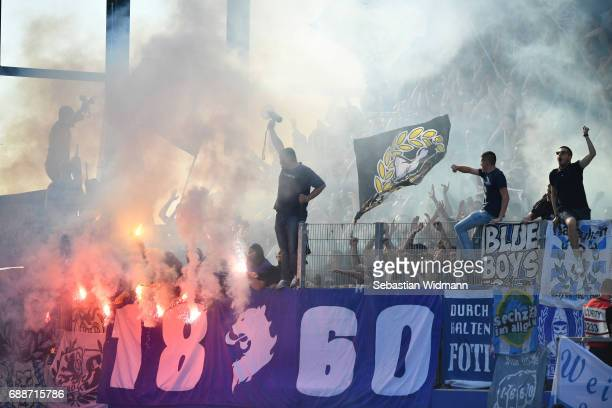 Supporters of 1860 Muenchen burn flares just prior to the Second Bundesliga Playoff first leg match between Jahn Regensburg and TSV 1860 Muenchen at...