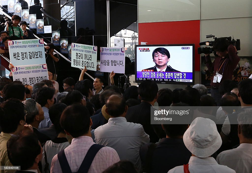 Supporters of Ahn Cheol Soo, chairman of Ahnlab Inc., look at a television screen as it broadcasts Ahn speaking during a news conference announcing his presidential candidacy in Seoul, South Korea, on Wednesday, Sept. 19, 2012. Ahn, founder of South Korea's biggest antivirus software maker, said he will run as an independent in the December presidential race to succeed Lee Myung Bak. Photographer: SeongJoon Cho/Bloomberg via Getty Images