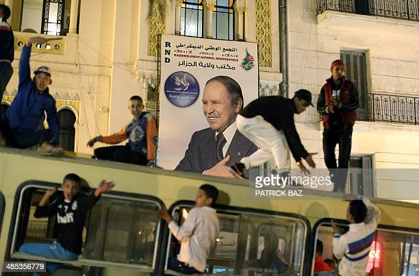 Supporters of Algerian President and candidate to the presidential elections Abdelaziz Bouteflika ride on the top of a bus as they celebrate in...