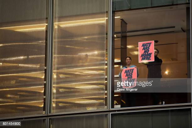 Supporters of antiTrump protestors hold up signs inside Trump Tower ahead of President Donald Trump's arrival August 14 2017 in New York City...
