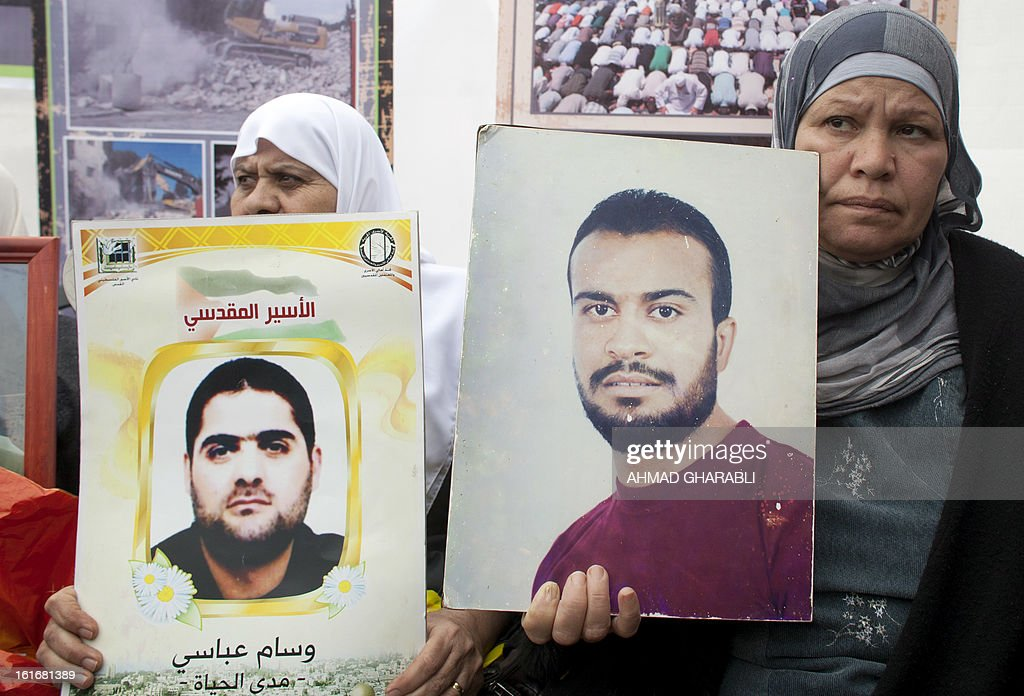 Supporters of Arab-Israeli Islamist leader Sheikh Raed Salah, carry portraits of imprisoned relatives during a press conference by Sheikh Raed (not in picture) in east Jerusalem, on February 14, 2013. A United Nations official expressed concern about the well being of Palestinian detainees in Israeli prisons and in particular about the condition of hunger striker Samer Issawi. AFP PHOTO/AHMAD GHARABLI