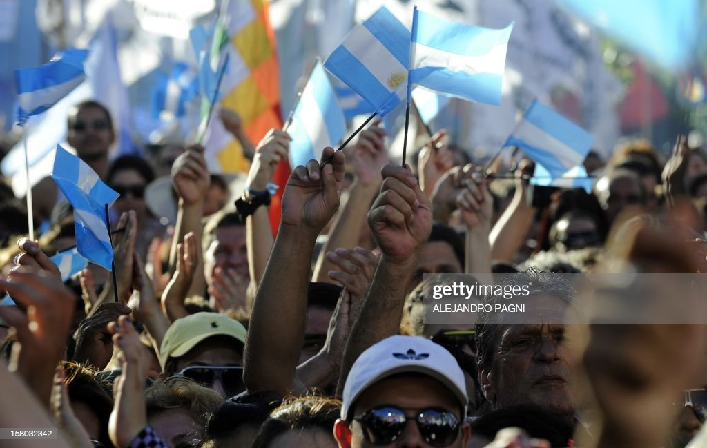 Supporters of Argentina's President Cristina Fernandez de Kirchner wave flags at Plaza de Mayo, on December 9, 2012, during a rally on the eve of the Day of Democracy and Human Rights, called by the government to celebrate the 29th anniversary of the return to democracy in Argentina. AFP PHOTO / Alejandro PAGNI