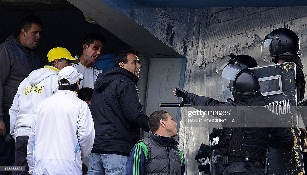 Supporters of Argentine team Boca Juniors argue with Uruguayan riot policemen upon their arrival at Centenario Stadium in Montevideo, where Boca will face Uruguay's Nacional in a Libertadores Cup football match on March 14, 2013. AFP PHOTO/Pablo PORCIUNCULAn