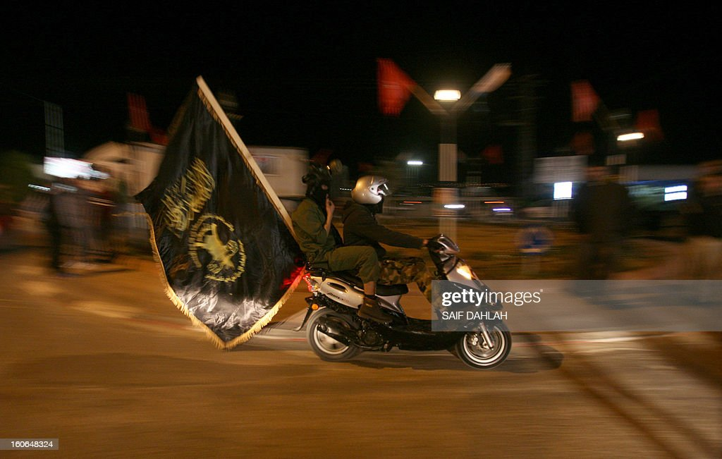Supporters of Bassam Saadi, leader of the West Bank Islamic Jihad movement drive a scooter celebrating with a black flag of jihad after Saadi was released from an Israeli jail, on February 4, 2013 in the West Bank city of Jenin.