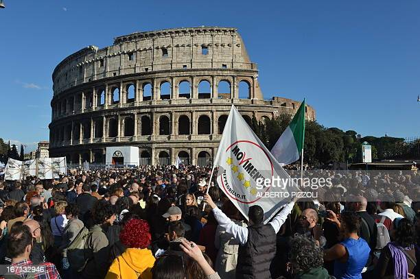 Supporters of Beppe Grillo's FiveStar Movement hold a flag of his party in front of the Colisseum during a rally in central Rome on April 21 2013...
