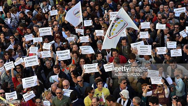 Supporters of Beppe Grillo's FiveStar Movement hold placards as they protest against Giorgio Napolitano's election as president during a rally in...