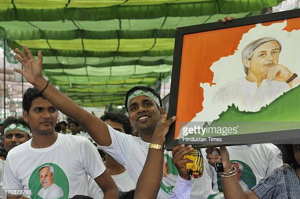 Supporters of BJD holdinh portrait of Odisha Chief Minister Naveen Patnaik during massive Swabhiman rally at Ramlila Maidan on June 12 2013 in New...