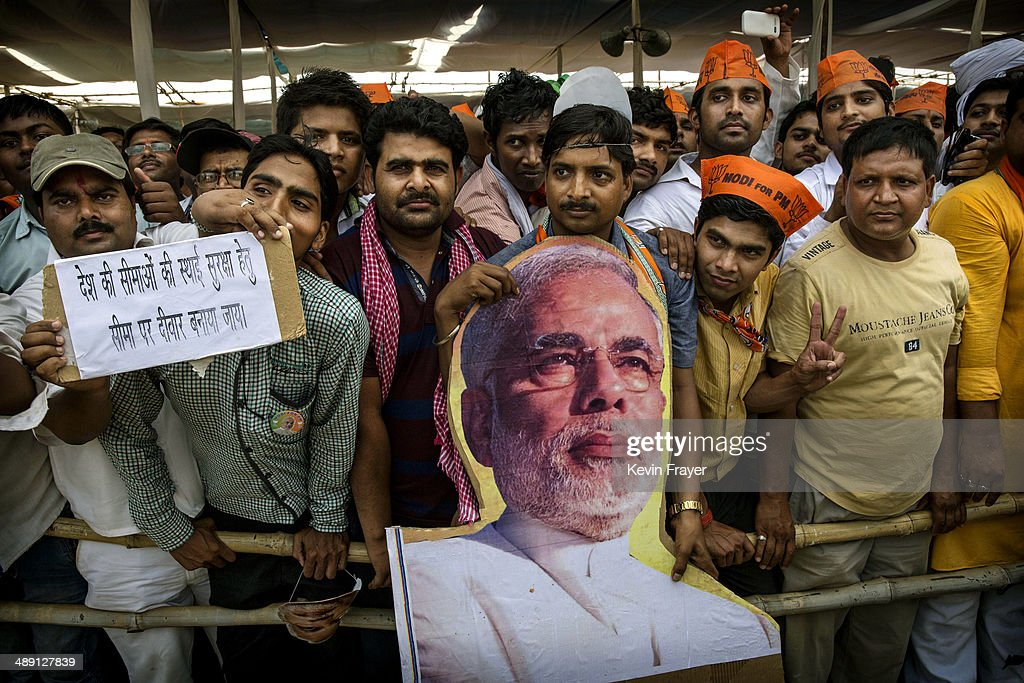 Supporters of BJP leader Narendra Modi listens as he speaks at a rally on May 10 2014 in Robertsganj near Varanasi India India is in the midst of a...