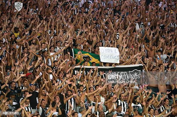 Supporters of Brazil's Botafogo hold a banner reading 'God is with us' and a sign reading 'The Pope is with them' during their 2014 Copa Libertadores...