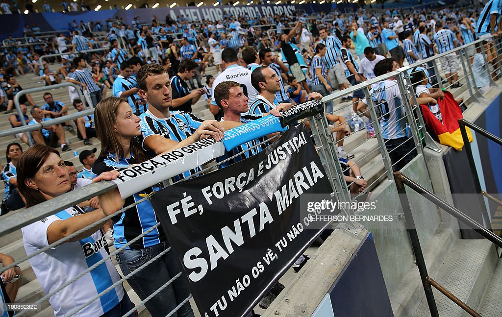 Supporters of Brazil's Gremio display a banner in homage to the victims of the fire in a nightclub in Santa Maria, before the start of the Copa Libertadores football match against Ecuador's Liga de Quito, at the Arena do Gremio stadium in Porto Alegre, Brazil, on January 30, 2013. AFP PHOTO / Jefferson BERNARDES