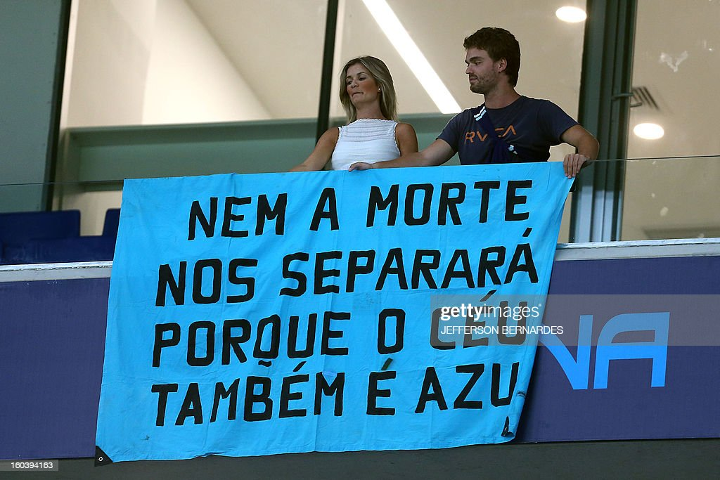 Supporters of Brazil's Gremio display a banner in homage to the victims of the fire in a nightclub in Santa Maria, before the start of the Copa Libertadores football match against Ecuador's Liga de Quito, at the Arena do Gremio stadium in Porto Alegre, Brazil, on January 30, 2013. Banner reads 'Not even death can part us because the sky -heaven- is also blue'. AFP PHOTO / Jefferson BERNARDES