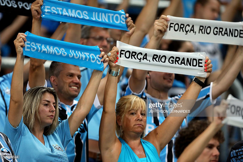 Supporters of Brazil's Gremio display signs in homage to the victims of the fire in a nightclub in Santa Maria, before the start of the Copa Libertadores football match against Ecuador's Liga de Quito, at the Arena do Gremio stadium in Porto Alegre, Brazil, on January 30, 2013. AFP PHOTO / Jefferson BERNARDES
