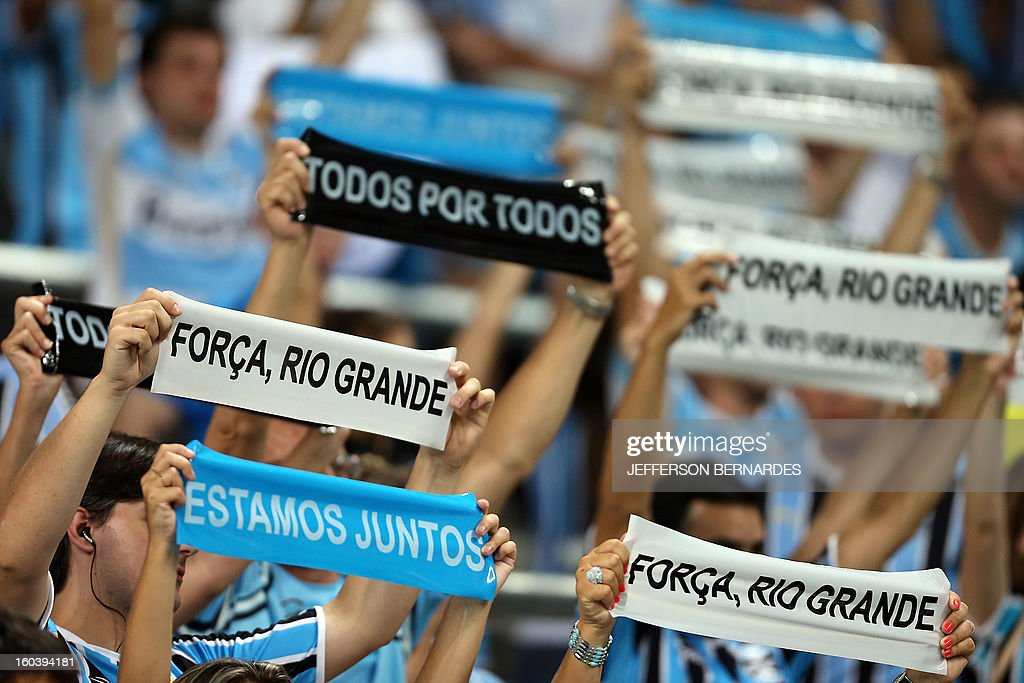 Supporters of Brazil's Gremio raise signs in homage to the victims of the fire in a nightclub -earlier this week- in Santa Maria, before the start of the Copa Libertadores football match against Ecuador's Liga de Quito, at the Arena do Gremio stadium in Porto Alegre, Brazil, on January 30, 2013. Banner reads 'Not even death can part us because the sky -heaven- is also blue'. AFP PHOTO / Jefferson BERNARDES
