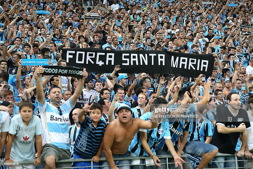 Supporters of Brazil's Gremio raise signs in homage to the victims of the fire in a nightclub -earlier this week- in Santa Maria, before the start of the Copa Libertadores football match against Ecuador's Liga de Quito, at the Arena do Gremio stadium in Porto Alegre, Brazil, on January 30, 2013. AFP PHOTO / Jefferson BERNARDES