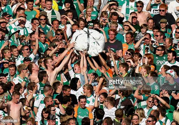 Supporters of Bremen hold a paper ball during the Bundesliga match between Werder Bremen and Hamburger SV at the Weser stadium on May 10 2009 in...