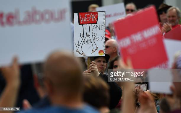 Supporters of Britain's main opposition Labour party hold a banner reading 'Weak and Wobbly' referring to Britain's Prime Minister Theresa May as the...