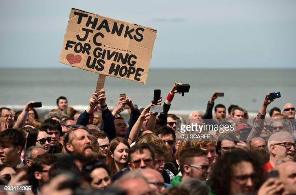 Supporters of Britain's main opposition Labour Party hold placards as the leader Jeremy Corbyn speaks during a campaign visit in Colwyn Bay north...