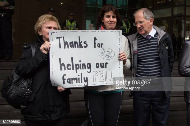 Supporters of Cardinal George Pell hold a placard outside the court during Cardinal George Pell's court hearing at the Melbourne Magistrates Court in...