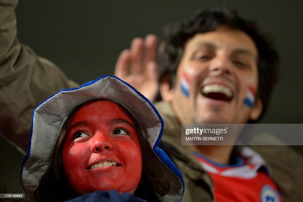 Supporters of Chile cheer for their team before the start of the Brazil 2014 FIFA World Cup South American qualifier match against Venezuela, in Santiago, on September 6, 2013. AFP PHOTO / MARTIN BERNETTI